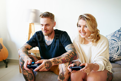 Buy stock photo Shot of a happy young couple playing video games together at home