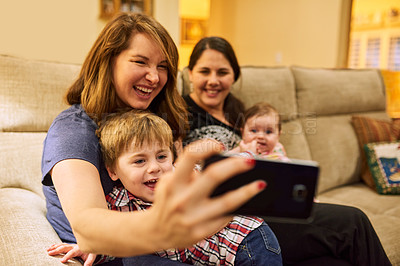 Buy stock photo Cropped shot of two mothers taking a selfie with their adorable children on the couch at home
