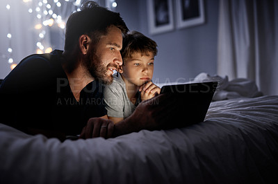 Buy stock photo Shot of a father and his little son using a digital tablet together in bed at night