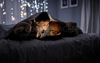 Buy stock photo Shot of an adorable little boy using a digital tablet in bed at night