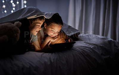Buy stock photo Shot of two adorable little siblings using a digital tablet together in bed at night