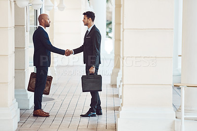 Buy stock photo Shot of two businessmen shaking hands in the city