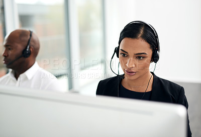 Buy stock photo Shot of a call centre agent working in an office alongside her colleague