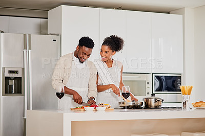 Buy stock photo Cropped shot of a young couple cooking in the kitchen