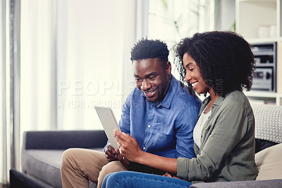 Buy stock photo Cropped shot of a young couple using a digital tablet together at home