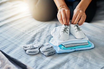 Buy stock photo Closeup shot of a pregnant woman sorting baby clothes at home