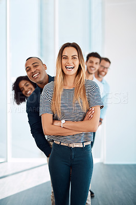 Buy stock photo Cropped portrait of an attractive young businesswoman standing in front of her creative colleagues in their modern office
