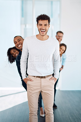 Buy stock photo Cropped portrait of a handsome young businessman standing in front of his creative colleagues in their modern office