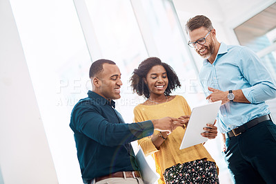 Buy stock photo Low angle shot of three creative colleagues working on a tablet together in their modern office