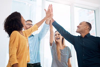 Buy stock photo Cropped shot of a group of creative colleagues high fiving in celebration in their modern office