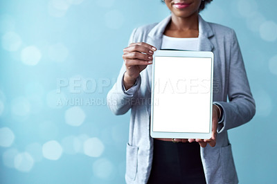 Buy stock photo Cropped studio shot of a young businesswoman holding a digital tablet with a blank screen against a blue background