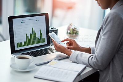 Buy stock photo Shot of a businesswoman using a mobile phone and laptop with graphs on it in a modern office