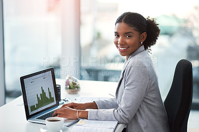Buy stock photo Shot of a young businesswoman using a laptop with graphs on it in a modern office