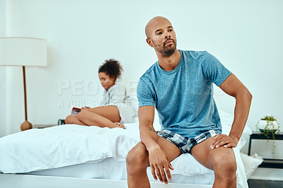 Buy stock photo Shot of a young couple sitting apart after having an argument