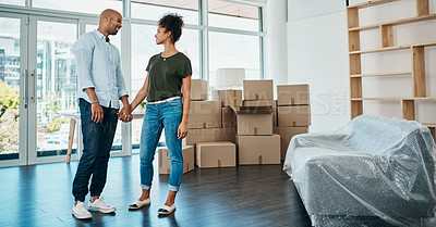 Buy stock photo Shot of a young couple holding hands while moving house