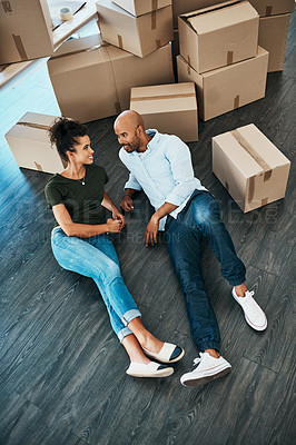 Buy stock photo Shot of a young couple taking a break while moving house