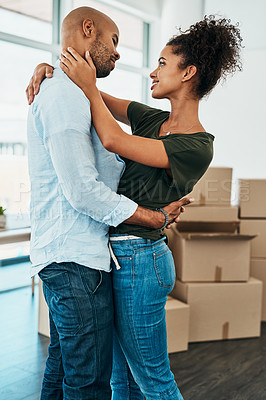 Buy stock photo Shot of a young couple hugging each other while moving house