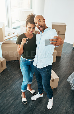 Buy stock photo Shot of a young couple taking a selfie while holding the keys to their new home