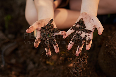 Buy stock photo Cropped shot of an unrecognizable little boy's hand's holding soil outside