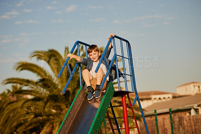 Buy stock photo Cropped shot of an adorable little boy sliding down a slide at a playground outside
