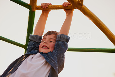 Buy stock photo Cropped shot of an adorable little boy playing on the jungle gym at a playground outside
