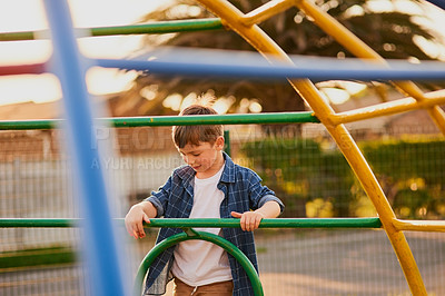 Buy stock photo Cropped shot of an adorable little boy playing at a playground outside