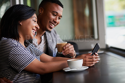 Buy stock photo Shot of a young couple using a mobile phone together on a date in a cafe
