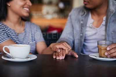 Buy stock photo Cropped shot of a young couple holding hands on a date in a cafe