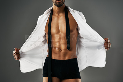Buy stock photo Studio shot of a sexy unrecognizable man showing off his abs against a gray background