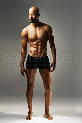 Buy stock photo Studio shot of a sexy young man against a gray background in his underwear