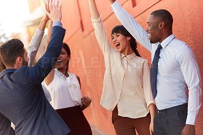 Buy stock photo Shot of a group of businesspeople high fiving together outdoors