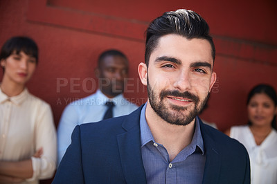 Buy stock photo Portrait of a young businessman standing outside with his colleagues in the background