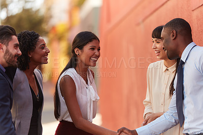 Buy stock photo Shot of businesspeople shaking hands while out in the city