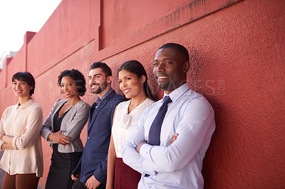 Buy stock photo Shot of a group of businesspeople standing against a red wall outdoors