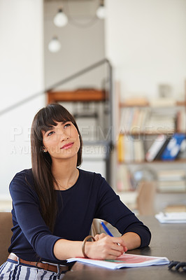 Buy stock photo Shot of a young businesswoman working through paperwork and looking thoughtful her desk in a modern office