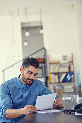 Buy stock photo Shot of a young businessman working through paperwork her desk in a modern office