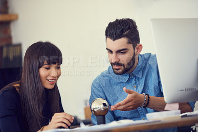 Buy stock photo Shot of a young businessman and businesswoman working together on a new design in a modern office