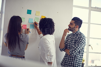 Buy stock photo Shot of a group of businesspeople having a brainstorming session on a wall in a modern office