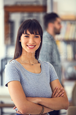 Buy stock photo Portrait of a confident young businesswoman with her colleagues working in the background of a modern office