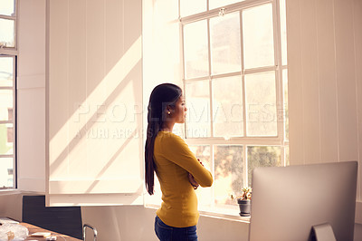 Buy stock photo Shot of a young businesswoman looking thoughtfully out of a window in a modern office