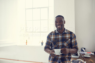 Buy stock photo Shot of a young businessman enjoying a coffee break in a modern office