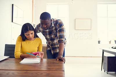 Buy stock photo Shot of a young businessman and businesswoman using a mobile phone together in a modern office