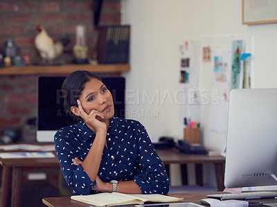 Buy stock photo Shot of a young businesswoman looking thoughtful while working at her desk in a modern office