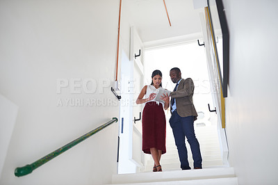 Buy stock photo Shot of two businesspeople using a digital tablet in an office