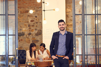 Buy stock photo Portrait of a young businessman standing in an office with his colleagues in the background