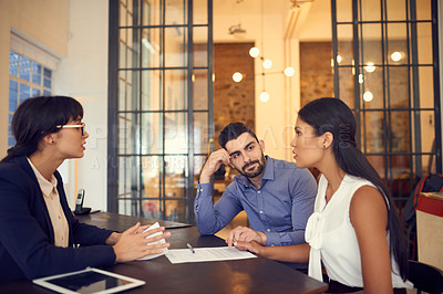 Buy stock photo Shot of a young couple meeting with a financial planner in an office