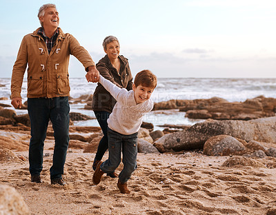 Buy stock photo Full length shot of an adorable little boy leading his grandparents by the hand on the beach