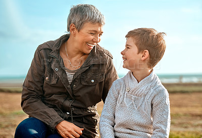 Buy stock photo Cropped shot of an adorable little boy and his grandmother sitting outside at the beach