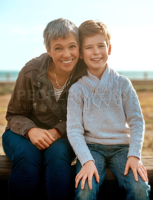 Buy stock photo Cropped portrait of an adorable little boy and his grandmother sitting outside at the beach