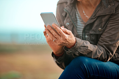 Buy stock photo Cropped shot of an unrecognizable woman using her cellphone while sitting outside
